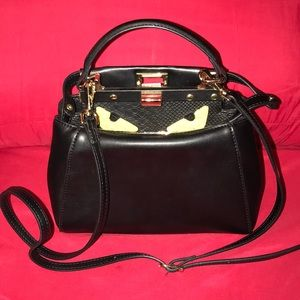 Black leather handbag with yellow eyes. Never worn